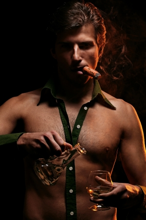 Artistic picture of handsome man with naked torso smoking cigar and drinking wine Stock Photo - 16821505