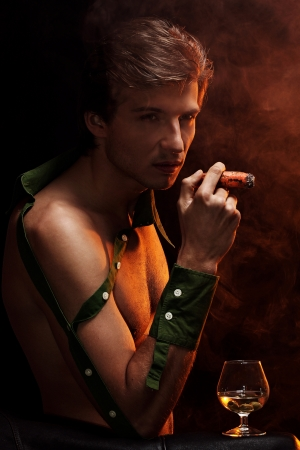 Artistic picture of handsome man with naked torso smoking cigar and drinking wine Stock Photo - 16821510