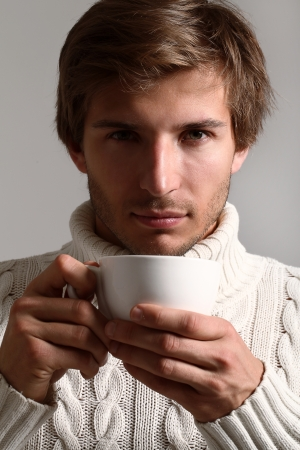 Handsome and beautiful man in white sweater drinking tea Stock Photo - 16821527