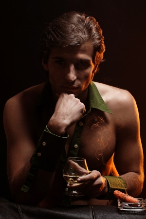 Artistic picture of handsome man with naked torso smoking cigar and drinking wine Stock Photo - 16821511