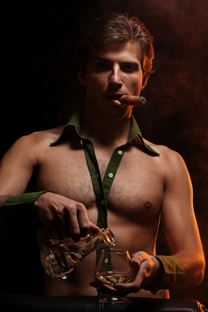 Artistic picture of handsome man with naked torso smoking cigar and drinking wine Stock Photo - 16821520