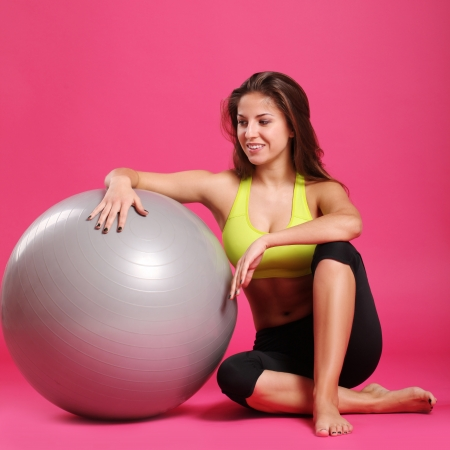 Close up of happy and beautiful woman with fitness ball isolated on a pink photo