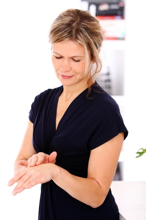 Beautiful mid aged woman applying cream on a hand photo