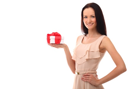Beautiful young girl smiling and holding gift over a white background photo
