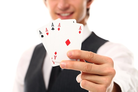 Handsome young man holding playing cards in hand photo