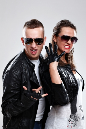 Young brutal couple in leather and sunglasses in studio photo