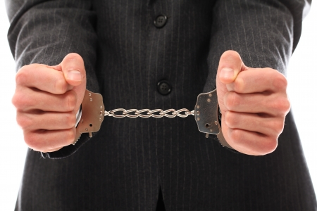fettered: Close up of businessman hands in handcuffs over a white background Stock Photo