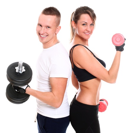 Young smiling couple lifting dumbbells in studio over a white background photo