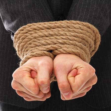 Close up of businessman hands tied with rope together photo