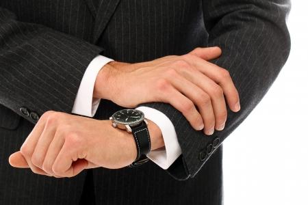 punctual: Cerca de las manos del hombre de negocios comprobando sus relojes sobre un fondo blanco