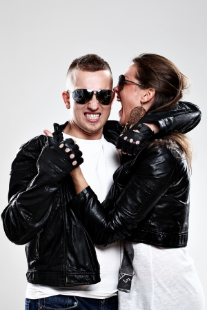 leather glove: Young brutal couple in leather and sunglasses in studio
