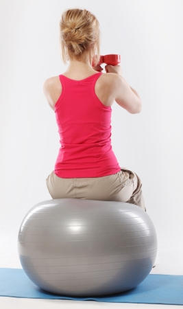 Woman sitting on a ball and doing exercise with dumbbells view from the back photo
