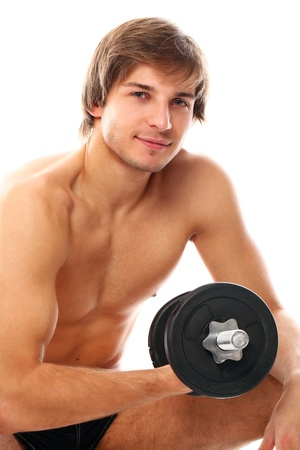 Handsome and sporty guy lifting dumbbell over a white background photo