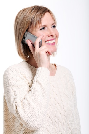 Caucasian middle aged woman talking by cellphone smiling over white background photo