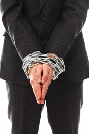 Close up of businessman hands chained over a white background photo