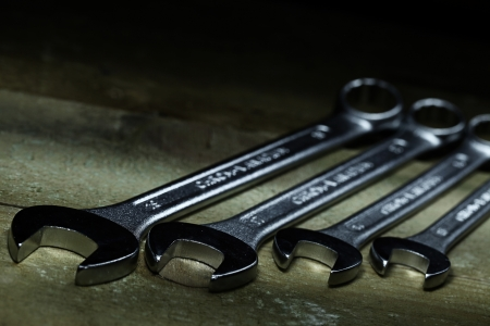 Closeup of iron spanners set over wooden surface photo