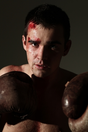 blood sport: Handsome man in boxing gloves with blood on a face Stock Photo