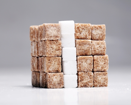 square of brown and white sugar cubes stacked up over a grey stock