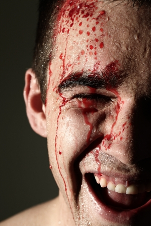 scamp: Close up of handsome laughing man face in blood Stock Photo