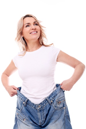 weightloss: Happy mid aged woman in big pants after weight losing