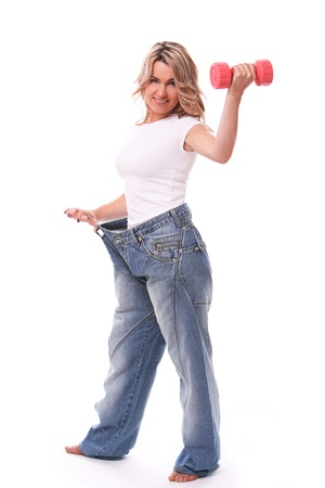 losing loss: Happy mid aged woman in big pants after weight losing with dumbbell in hand