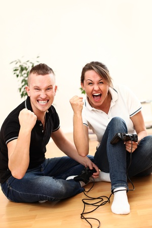 passion play: Young couple emotionally with passion play video games at home on the floor