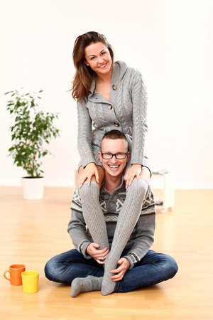 Young and happy smiling woman sitting on man s shoulders at home photo