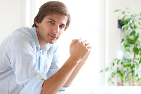 Handsome young man in blue office shirt thinking about future photo