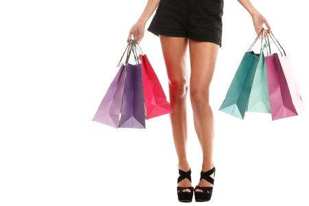 chicas de compras: Close up de piernas de la mujer sexy en zapatos y bolsos de compras aislados sobre un fondo blanco Foto de archivo