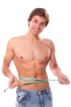 Sexy and handsome man measuring his belly after weight lose over a white background Stock Photo - 16934771