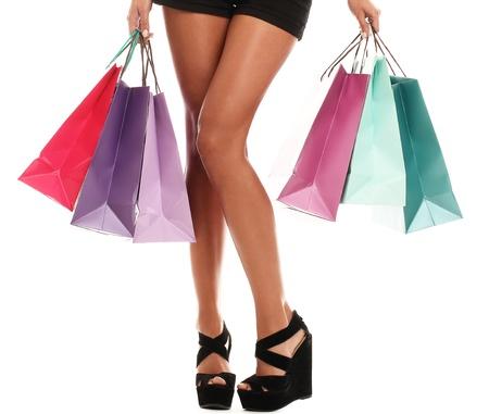 belles jambes: pr�s des jambes de femme sexy dans des chaussures et des sacs � provisions isol�s sur un fond blanc