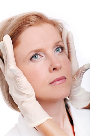 Close up of woman face and doctor gloves isolated on a white photo