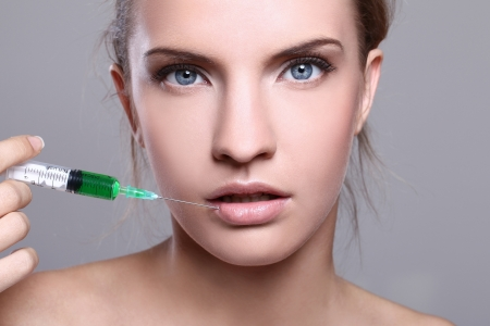 Close up of beautiful woman gets an injection in her face photo