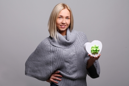 Attractive young blonde smiling with gift in hands over a grey background photo
