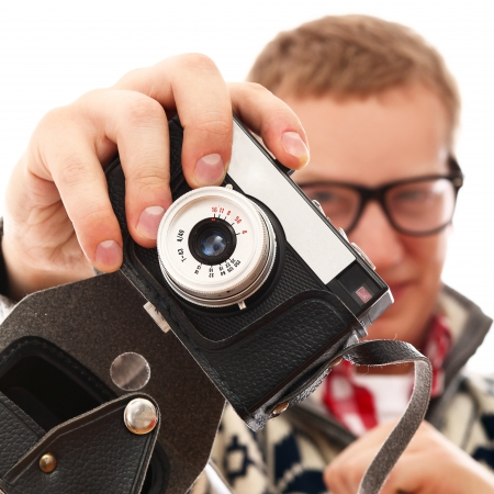 Young photographer with old camera make a photo shoot of you isolated on a white Stock Photo - 16997834