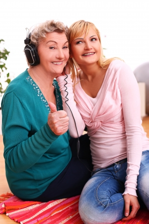 Granny and granddaughter listening music at home photo