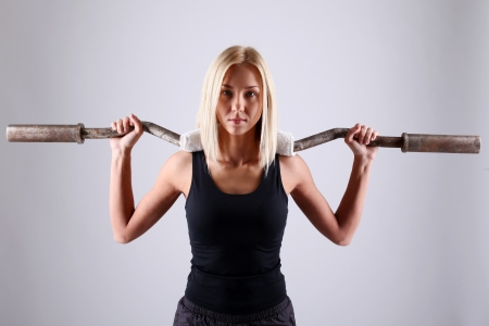Slim and sporty young blonde doing fitness exercise with fitbar in studio Stock Photo - 16997643