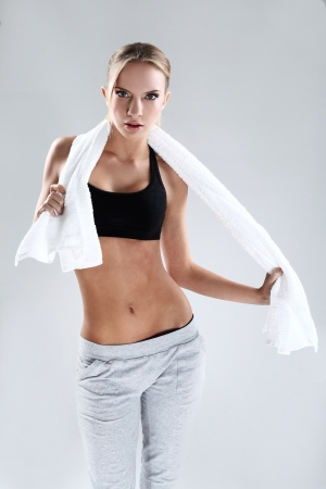 Slim and young fitness woman with towel in studio photo