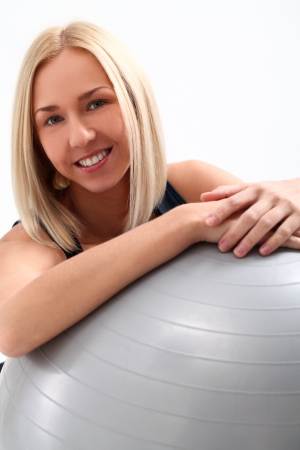 Close up of happy and beautiful woman with fitness ball isolated on a white photo
