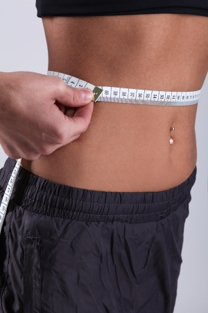 Close up of slim blonde stomach measuring waist with ruler over a grey background photo