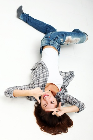 Attractive woman making frame with her hands lying on a white floor photo