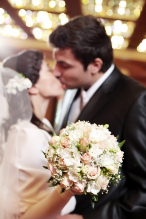 Beautiful and happy couple with flowers in hands get married indoors