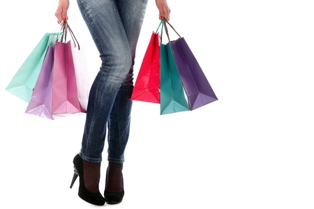 Shopping bags near legs in jeans and high heels over white background photo
