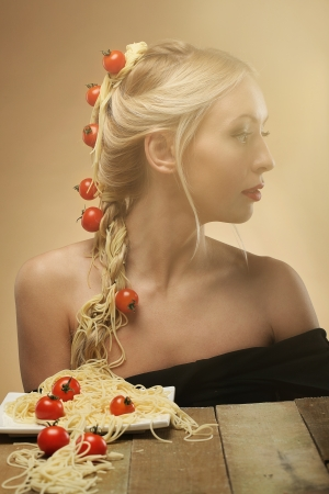 Art photo of young beautiful woman with pasta and tomatoes in her hair photo