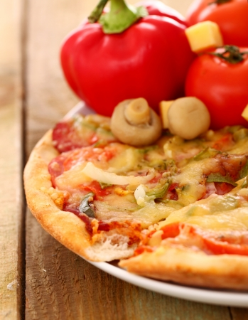 Fresh italian pizza in plate on a wooden surface Stock Photo - 17110924