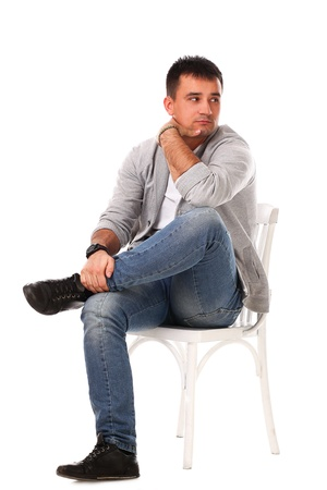 Young caucasian handsome man sitting on the chair isolated over white background Stock Photo