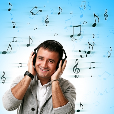 Young caucasian handsome man listening music isolated over background with notes Stock Photo - 17133199