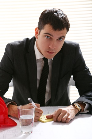 Young handsome engineer at workplace in office photo