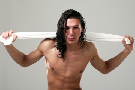 Young sexy man with long hair and towel isolated on white background photo