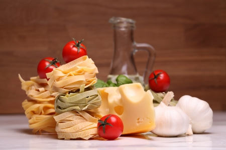 Fresh ingredients for pasta isolated on wooden background photo